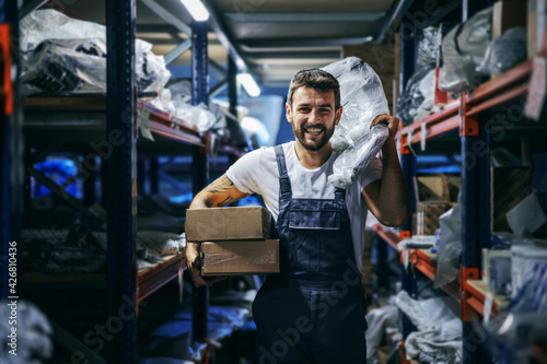 Carta da parati Smiling bearded tattooed hardworking blue collar worker in overalls holding boxes and bag and relocating them while walking in storage of import and export firm