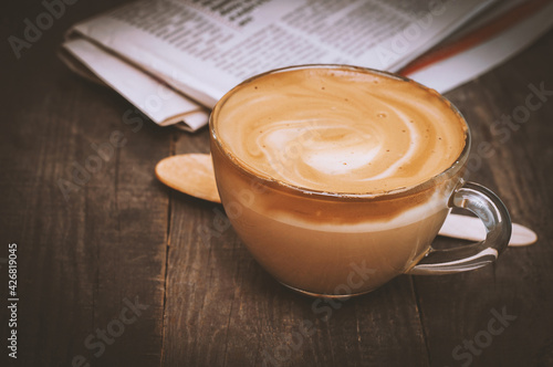 Fotografia Glass cup of coffee milk or cappuccino on the background of a newspaper on a dark brown wooden table