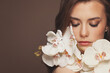 Attractive model woman with healthy clear skin and spring orchid flowers. Facial treatment and skin care concept