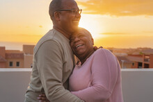 Happy Latin Senior Couple Having Romantic Moment Embracing On Rooftop During Sunset Time - Elderly People Love Concept