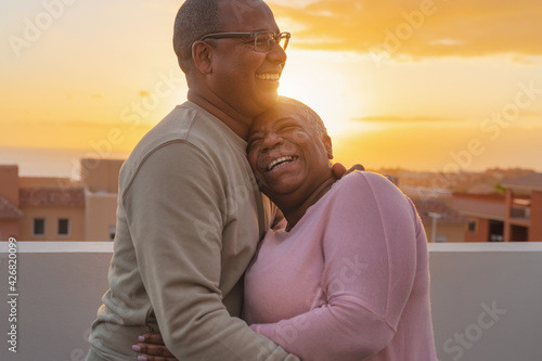 Obraz na plátně Happy Latin senior couple having romantic moment embracing on rooftop during sun