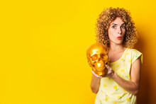 Surprised Curly Young Woman Holding Golden Skull On Yellow Background.