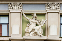 Art Nouveau Sculpture At Building Facade. Sculpture Of Women Playing Musical Instrument Lyre Harp And Singing Between Two Columns. Facade Art In Riga, Latvia, Europe.