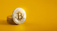 A Bitcoin Resting On A Pile Of Bitcoins On A Yellow Background And Copy Space. Golden BTC Coin, Stock Market Of Cryptocurrencies And Decentralized Finances Concept