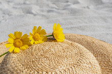 Close-up Yellow Flowers On A Straw Hat In A Sandy Beach.