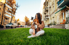 Attractive Young Woman Is Sitting On The Green Lawn On The City Street With Her Adorable Small Yorkie Terrier On A Sunny Autumn Day.