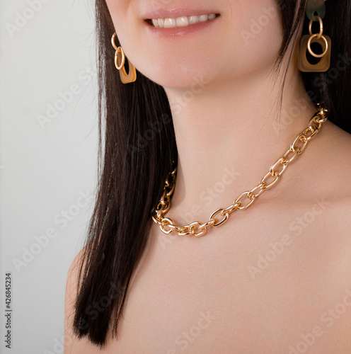 Fotografija portrait of a beautiful woman with earrings and a necklace in the form of a gold
