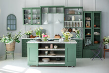 Green Kitchen Interior With Furniture. Stylish Cuisine With Flowers In Vase. Wooden Kitchen In Spring Decor. Cozy Home Decor. Kitchen Utensils, Dishes And Plate On Table. Kitchen Island In Dining Room