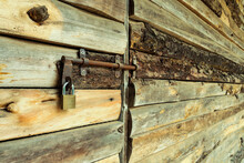 Wooden Door Closed With Rusty Lock And Padlock. Surface Of Rustic Wooden Strips In Perspective. Country Building Style.