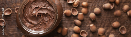 Fotografie, Obraz Chocolate-nut paste spread in a glass jar on a wooden background banner