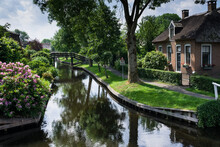 Landscape View Of Famous Giethoorn Village In The Netherlands With Canals, Bridges And Rustic Thatched Roof Houses In Farm Area