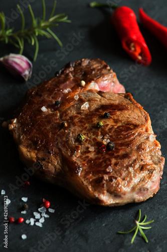 Fototapeta Grillowany stek wołowy z ziarnami pieprzu i ziołami na kamiennej desce obraz