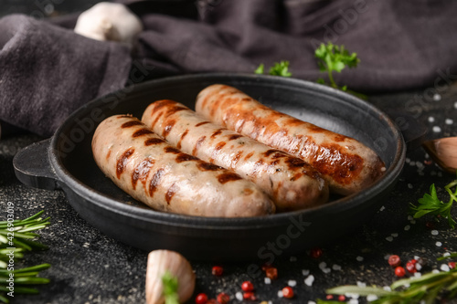Frying pan with delicious grilled sausages on dark background, closeup
