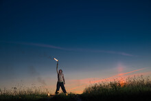 Man Stands With Signal Torches Against Dark Sunset Sky