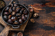 Roasted Chestnuts Served In A Pan On A Wooden Cutting Board. Wooden Background. Top View. Copy Space