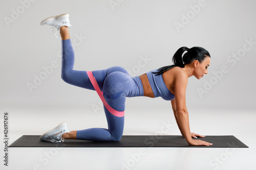 Fitness woman doing kickback exercise for glutes with resistance band on gray background Fototapeta