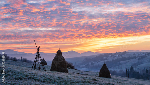 Photo First autumn frosts on pasture with haystacks and majestic sunrise in the mountains village outskirts