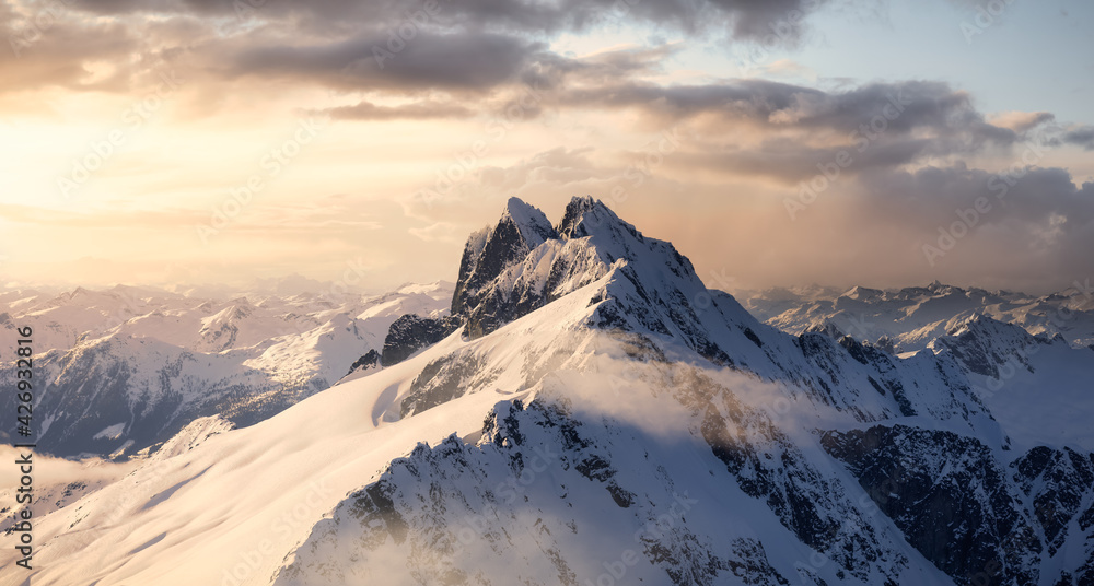 Fototapeta Aerial View from Airplane of Blue Snow Covered Canadian Mountain Landscape in Winter. Colorful Pink Sunset Sky Art Render. Tantalus Range near Squamish, North of Vancouver, British Columbia, Canada.