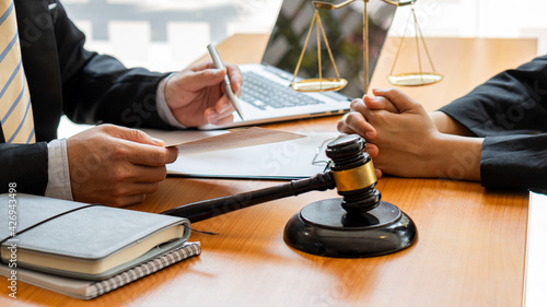 Obraz na plátne The judge hammer and the scales of a fair uncle on a table where a lawyer advises clients