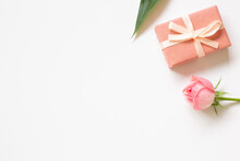 Gift Box And Rose Flower On White Background. Flat Lay, Top View, Copy Space