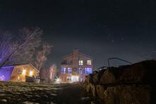 Lumière Provenant Des Fenêtres D'une Construction En Bois En Haut D'une Colline Lors D'une Nuit Avec Ciel étoilé