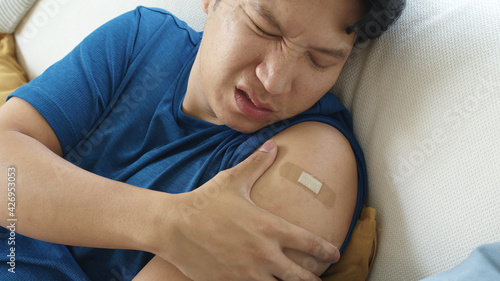 Fotografie, Obraz Close up young adult attractive hipster asia man receive covid-19 anti virus vaccine in campaign vaccination safe life got side effect pain at arm