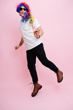 Feminine Man Playing Girl, Jumping Around And Playing Cute. Over Pink Background