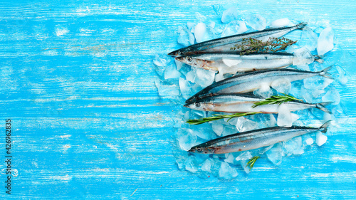 Raw Pacific fish Saury. Seafood. On a dark background.