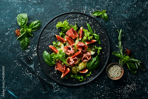 Green salad with prosciutto, cucumber and fig on a black stone plate. Food. Top view. Free space for your text.