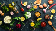 Set Of Sauces And Spices On Stone Background. Sauces: Mayonnaise, Ketchup, Tartare, Barbecue And Chili Sauce In Bowls.