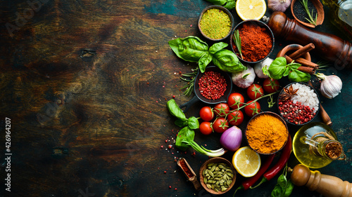 Fototapeta Fragrant spices, herbs and basil on a dark wooden background. Top view. Free space for text. obraz