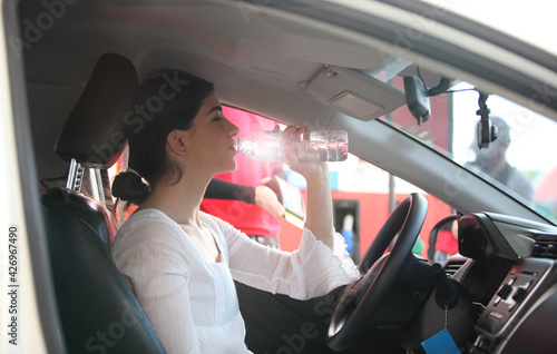 Obraz na plátne woman drinks Water in the Car, Thirsty Behind the Wheel , Woman driver drinks water from a refillable bottle in her car, thirsty behind the wheel, stopped to rest