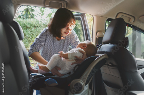 Fotografia Asian young mother putting her baby son into car seat