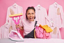 Cleaning Washing And Ironing Concept. Annoyed Housewife Holds Mop And Laundry Basket Going To Iron Clothes Has Much Work About House Expresses Negative Emotions. Female Housekeeper Does Domesic Chores