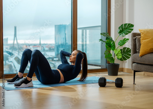 Photographie Sportive brunette woman does crunches on glazed balcony