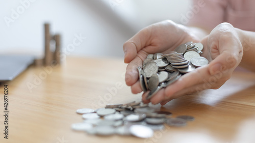Fényképezés Woman's hand full of coins, Business people saving money for future investment, saving money, Silver baht coins,Finance and investment, including taxes, Spending money like maturity concept