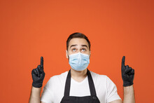 Young Man Barista Barman Employee In Apron White T-shirt Face Mask Coronavirus Covid-19 Pandemic Quarantine Work Coffee Shop Point Finger Up Workspace Isolated On Orange Background Business Startup.