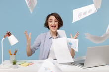 Young Excited Surprised Sad Director Employee Business Woman In Casual Shirt Sit Work At White Office Desk With Pc Laptop Throwing Up Paper Account Documents Isolated On Pastel Blue Background Studio.