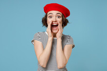Young Expressive Excited Fun European Woman 20s With Short Hairdo Wear French Beret Red Hat Striped T-shirt Scream News With Hands Near Mouth Isolated On Pastel Blue Color Background Studio Portrait.