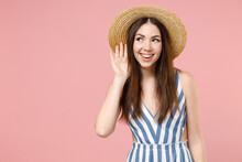 Young Curious Nosy Smiling Woman 20s Wearing Summer Clothes Striped Dress Straw Hat Try To Hear You Overhear Listening Intently Isolated On Pastel Pink Background Studio. People Lifestyle Concept.