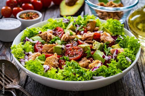 Fototapeta Tuna salad - tuna, cherry tomatoes, avocado, lettuce and onion on wooden table  obraz
