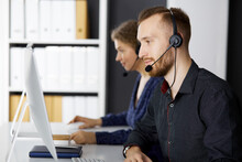 Bearded Businessman Talking By Headset Near His Female Colleague While Sitting In Modern Office. Diverse People Group In Call Center. Telemarketing And Customer Service