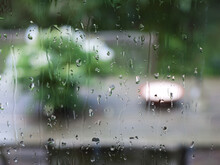 Rain Drops On Glass Window With Green Blurred Background Of Garden