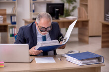 Old Male Employee Auditor Wearing Many Glasses At Workplace