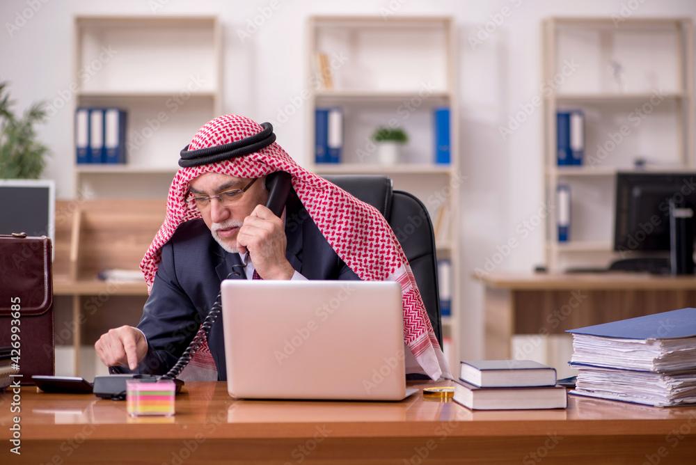 Fototapeta Aged arab businessman employee sitting at workplace