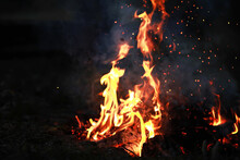 Burning Red Hot Sparks Fly From Big Fire. Burning Coals, Flaming Particles Flying Off Against Black Background.