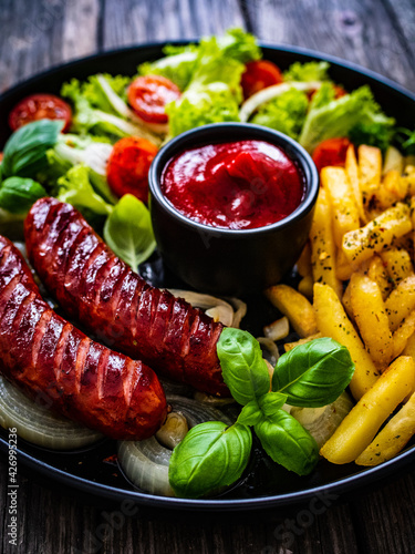 Fried sausages, French fries, onion and fresh vegetables on black table