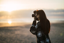 Chica Morena De Espaldas Tomando Una Foto Con Una Camara Reflex Al Atardecer En La Playa
