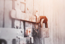 On The Gray Old Wooden Gate Is A Rusty Latch, On Which Hangs An Old Metal Lock, Illuminated By Sunlight. Closed.
