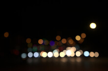 Blurry Floating Bokeh Combination Of Cars On The Road And Street Lights At The Intersection, Outdoor In Modern Big City. Beautiful Blurred Lights Of Dark Night Abstract. Horizontal, Front View.